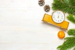De achtergrond van het nieuwjaar of van Kerstmis Vertakt de de winter Retro wekker zich met pijnboom, kegels op witte houten hoog stock foto's