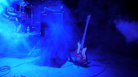 De achtergrond van het rotsoverleg Elektrogitaar verlaten op het stadium Rook bij het overleg Muzieklichten bij nachtclub, overle stock video