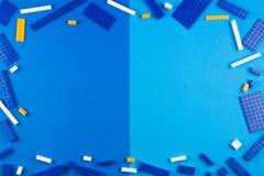 De achtergrond van het speelgoed Blauwe, witte en gele plastic bouwblokken op blauwe achtergrond Royalty-vrije Stock Afbeelding