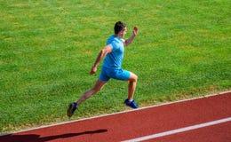 De achtergrond van het het spoorgras van de atletenlooppas Sprinter opleiding bij stadionspoor De agent ving in midair Korte afst stock afbeeldingen
