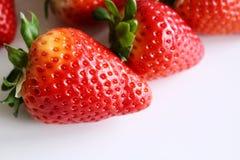 De achtergrond van het voedsel Close-up op vers organische rode rijpe aardbeien die op een witte achtergrond liggen De zomer rijp Stock Afbeelding