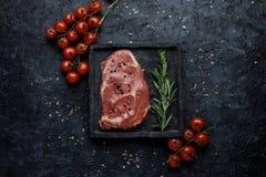 De achtergrond van het voedsel Het ruwe lapje vlees van het riboog met tomaten en rozemarijn op zwarte hoogste mening als achterg royalty-vrije stock foto's