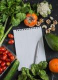 De achtergrond van het voedsel Verse groenten, vruchten, en lege blocnote op een donkere achtergrond Royalty-vrije Stock Foto's