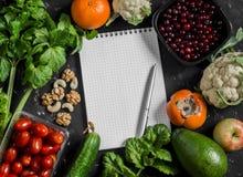 De achtergrond van het voedsel Verse groenten, vruchten en lege blocnote op een donkere achtergrond Concept het gezonde eten Stock Foto
