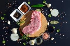 De achtergrond van het voedsel Vlees op een een knipselraad en peper, laurierblad, rozemarijn, uien, Himalayan-zout, olijfolie, s Royalty-vrije Stock Fotografie
