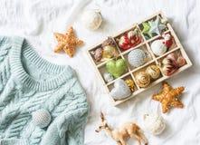De achtergrond van Kerstmis Doos van uitstekende Kerstmisdecoratie en blauwe gebreide sweater op het bed, mening van hierboven Ke royalty-vrije stock foto