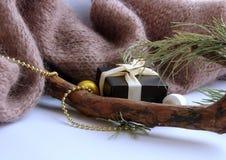De achtergrond van Kerstmis Een giftdoos met een beige lint bevindt zich keurig dichtbij de takken van de Kerstboom en het gebrei stock foto