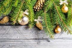 De achtergrond van Kerstmis Groene Spar met denneappels, gouden sneeuwvlokken, bal Royalty-vrije Stock Foto