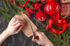 De achtergrond van Kerstmis Hoogste mening van aanwezig de omslagnieuwjaar van jong geitjehanden Ingepakte giften en rollen, nett Royalty-vrije Stock Afbeelding