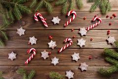De achtergrond van Kerstmis Kerstmisriet en koekjes in de vorm van sterren op een houten achtergrond Royalty-vrije Stock Afbeelding