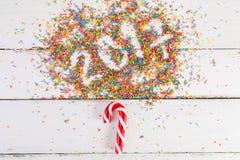 De achtergrond van Kerstmis Kerstmisriet op een witte houten achtergrond 2017 geschreven met Kleur het bestrooien Stock Fotografie