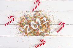 De achtergrond van Kerstmis Kerstmisriet op een witte houten achtergrond 2017 geschreven met Kleur het bestrooien Stock Foto