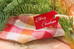 De achtergrond van Kerstmis De lijst is verfraaid met een mooi rood servet met een gele die kooi, door nette takken wordt omringd Stock Afbeelding
