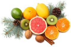 De achtergrond van Kerstmis de mengeling sneed citroen, groene kalk, sinaasappel, mandarin, kiwifruit en grapefruit met kegel en  royalty-vrije stock afbeeldingen