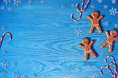 De achtergrond van Kerstmis Peperkoekmens, het riet van het Kerstmissuikergoed en sneeuwvlokken op blauwe houten achtergrond met  Stock Foto