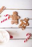 De achtergrond van Kerstmis Peperkoekmensen en Kerstmisriet op een witte houten achtergrond Stock Foto
