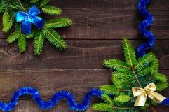 De achtergrond van Kerstmis Taksparren met helder lint op een donkere houten achtergrond worden verfraaid die Royalty-vrije Stock Afbeelding