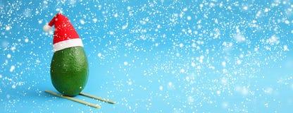 De achtergrond van de Kerstmisdecoratie met frsh groene avocado die in santahoed ski?en op heldere blauwe achtergrond Kaartconcep royalty-vrije stock foto's