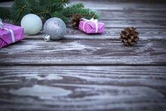 De achtergrond van de Kerstmisvakantie met giftenvakjes met spar vertakt zich, denneappels, Kerstmisballen op houten lijst royalty-vrije stock afbeelding