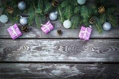 De achtergrond van de Kerstmisvakantie met giftenvakjes met spar vertakt zich, denneappels, Kerstmisballen op houten lijst Vlak l stock fotografie