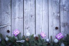 De achtergrond van de Kerstmisvakantie met giftenvakjes met spar vertakt zich, denneappels, Kerstmisballen op houten lijst Vlak l royalty-vrije stock foto