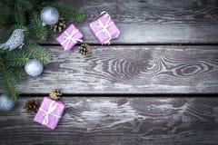 De achtergrond van de Kerstmisvakantie met giftenvakjes met spar vertakt zich, denneappels, Kerstmisballen op houten lijst Vlak l stock afbeelding