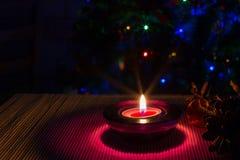 De achtergrond van de Kerstmisvakantie met purpere kaars en kleurrijke lichten Royalty-vrije Stock Afbeelding