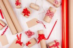 De achtergrond van Kerstmisvoorbereidingen - verpakkend document, giftvakjes, rode lint en bogen, streng als feestelijk patroon o royalty-vrije stock afbeeldingen