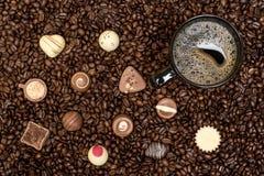 De achtergrond van koffiebonen en zwarte kop met pralines Royalty-vrije Stock Fotografie