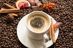 De achtergrond van koffiebonen met cofeekop, kaneel, en chocolade stock afbeeldingen