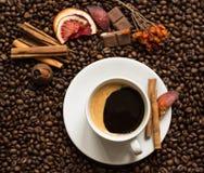 De achtergrond van koffiebonen met cofeekop, kaneel, en chocolade Stock Afbeelding