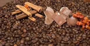 De achtergrond van koffiebonen met kaneel, en chocolade stock fotografie