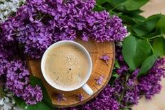 De achtergrond van de lente koffietribunes op een houten die hennep door lilac bloemen wordt omringd Stock Foto's