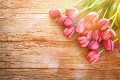 De achtergrond van Pasen Kleurrijke de lentetulpen op uitstekende houten beer stock afbeelding