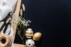 De achtergrond van Pasen De paaseieren in diverse gouden ontwerpen, schaar, bloemen en hennepbal over zwart verhaal schepen in De Stock Foto
