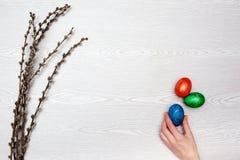 De achtergrond van Pasen Pussy wilgentakken en vrouwenhand met eieren Vlak leg, hoogste mening, exemplaarruimte Stock Foto's