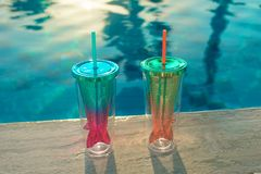 De achtergrond van de strandvakantie met twee cocktails in het glas dichtbij zwembad van de meerminstaart in luxueus hotel royalty-vrije stock foto
