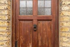 De achtergrond van uitstekend bruin geschilderd deur en van de kloppersleeuw hoofd kijkt die van ouderwets uitstekend messingsmet royalty-vrije stock afbeelding