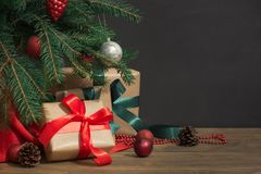 De Achtergrond van de Vakantie van Kerstmis Giften met een rood lint, een Kerstman` s hoed en een decor onder een Kerstboom op ee Stock Foto