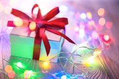 De Achtergrond van de Vakantie van Kerstmis Verpakte giftdoos met rood zijdelint en kleurrijke lichtenslinger over houten achterg stock foto