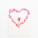 De achtergrond van valentijnskaarten Het symbool van het hart Bloemblaadjes van rozen en uitstekende document kaarten op witte ac Stock Afbeelding