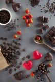 De achtergrond van de valentijnskaartendag met rode en donkere chocolade, harten a Stock Foto