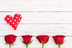 De achtergrond van de valentijnskaartendag met rode liefdehart en rozen bloeit op wit rustiek hout met exemplaarruimte stock afbeeldingen