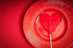 De achtergrond van de valentijnskaartendag met rode plaat en lolly met hartvorm op rode achtergrond royalty-vrije stock afbeelding