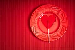 De achtergrond van de valentijnskaartendag met rode plaat en lolly met hartvorm op rode achtergrond stock foto