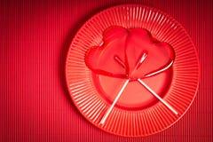 De achtergrond van de valentijnskaartendag met rode plaat en twee hart-vormige lollys op rode achtergrond stock fotografie