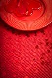 De achtergrond van de valentijnskaartendag met rood geribbeld document met rode plaat en hart-vormige lolly royalty-vrije stock foto