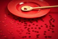 De achtergrond van de valentijnskaartendag met rood geribbeld document met rode plaat en houten lepel voor minnaars stock afbeelding
