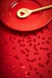 De achtergrond van de valentijnskaartendag met rood geribbeld document met rode plaat en houten lepel voor minnaars stock afbeeldingen