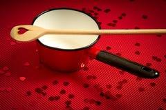 De achtergrond van de valentijnskaartendag met rood geribbeld document met rode steelpan en houten lepel voor minnaars stock foto